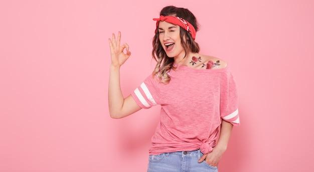 분홍색 배경에 고립 된 문신 hipster 여자의 초상화