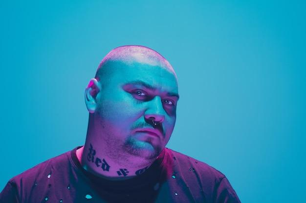 青い壁にカラフルなネオンの光で流行に敏感な男の肖像画。落ち着きと真面目なムードの男性モデル。