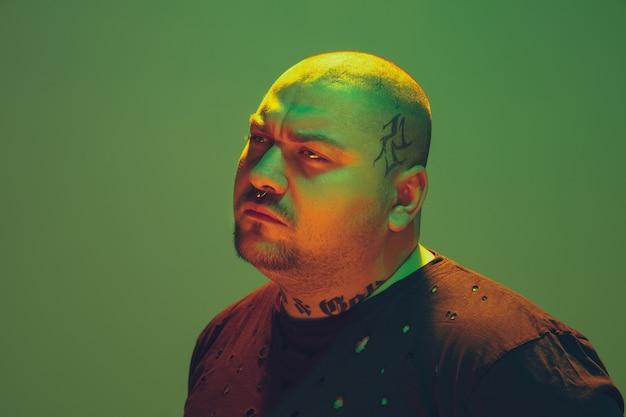 緑の背景にカラフルなネオンの光を持つ流行に敏感な男の肖像