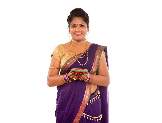 Портрет индийской традиционной девушки, держащей фотографию дии, дивали или дипавали с женскими руками, держащими масляную лампу во время фестиваля света на белом пространстве