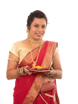 白の光の祭典の間にdiyaとプージャターリーを保持しているインドの伝統的な女の子の肖像画