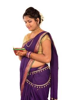 Портрет индийской традиционной женщины, держащей фото дия, дивали или дипавали с женскими руками, держащими масляную лампу во время фестиваля света