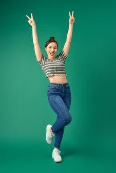 緑を飛び越えながら成功を祝う楽しい魅力的なアジアの女の子の肖像画。