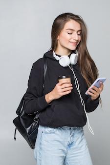 Портрет радостной привлекательной студентки с рюкзаком, слушающей музыку в наушниках, показывая пустой экран мобильного телефона и танцуя изолирован на белой стене