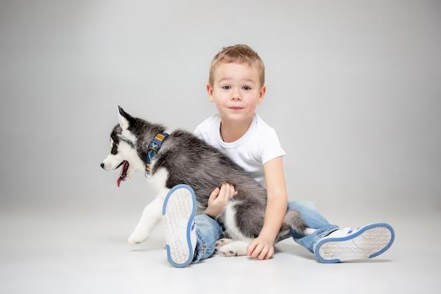 スタジオの床でシベリアンハスキーの子犬を楽しんでいるうれしそうな少年の肖像画。動物、友情、愛、ペット、子供時代、幸福、犬、ライフスタイルの概念