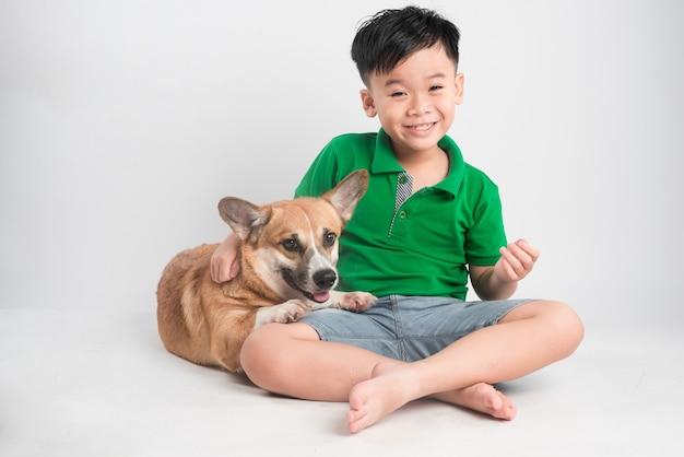 床にウェルシュコーギー犬を楽しんでいるうれしそうな少年の肖像画