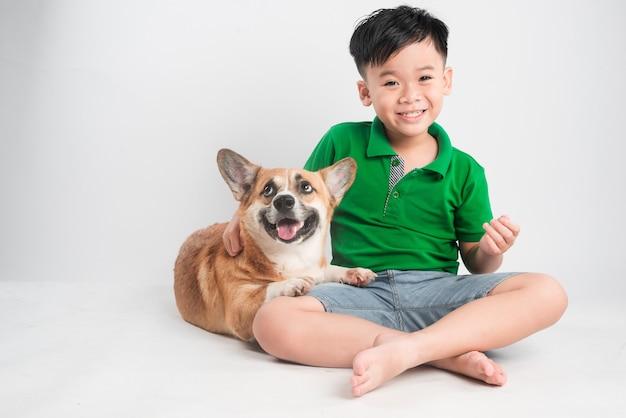 Портрет радостного маленького мальчика, развлекающегося с собакой вельш-корги на полу