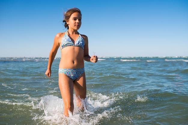 햇살 따뜻한 여름날에 바다에서 수영하는 즐거운 작은 긍정적 인 소녀의 초상화