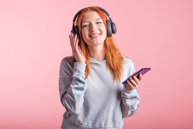 ピンクの背景のスタジオで彼女のスマートフォンでヘッドフォンで音楽を聴くうれしそうな赤毛の少女の肖像画