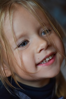 Портрет радостной романтической маленькой девочки с большими голубыми глазами и открытой улыбкой из восточной европы, крупный план, темный фон