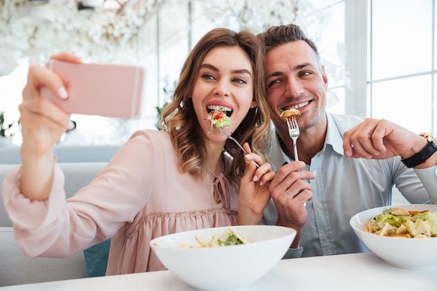 Портрет радостной молодой пары, делающей селфи
