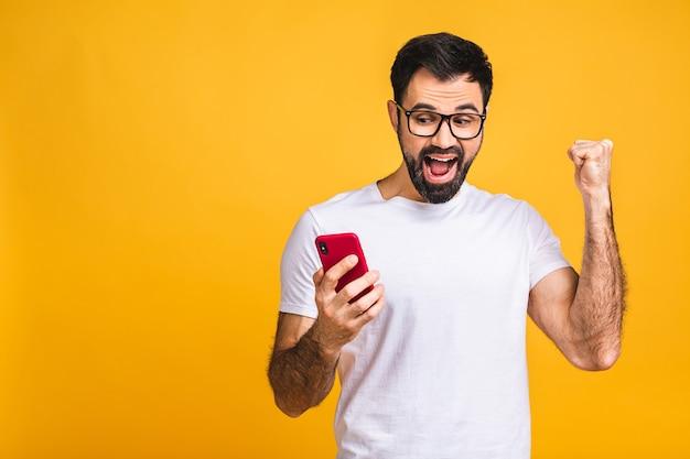 Портрет радостного молодого человека, держащего мобильный телефон на желтом фоне, празднуя победу.