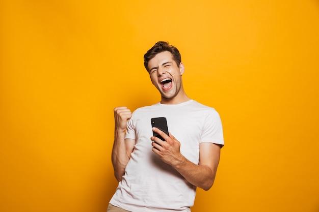 Портрет радостного молодого человека, держащего мобильный телефон