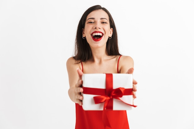 고립 된 선물 상자를 들고 빨간 드레스에 즐거운 젊은 여자의 초상화