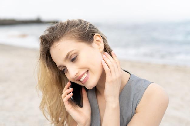 ビーチでかわいい笑顔で携帯電話で話しているうれしそうな若い女性の肖像画