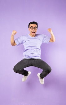 Портрет прыгающего азиатского мужчины, изолированного на фиолетовом фоне