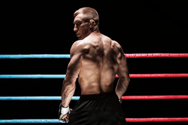 リングの背景にキックボクサーの肖像画。背面図。スポーツと総合格闘技の概念。ミクストメディア