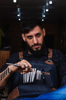 ラテンの床屋の肖像画。はさみとタトゥーでひげを生やしたヒップスター