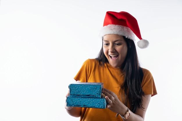クリスマスの帽子をかぶったラティーナの女性の肖像画は、贈り物に驚いています。白色の背景