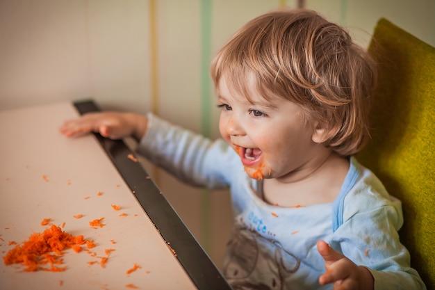 彼の手で明るいニンジンを食べて笑っている赤ちゃんの肖像画