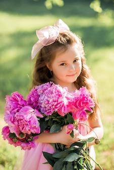 牡丹の花束と笑っている女の子の肖像画。