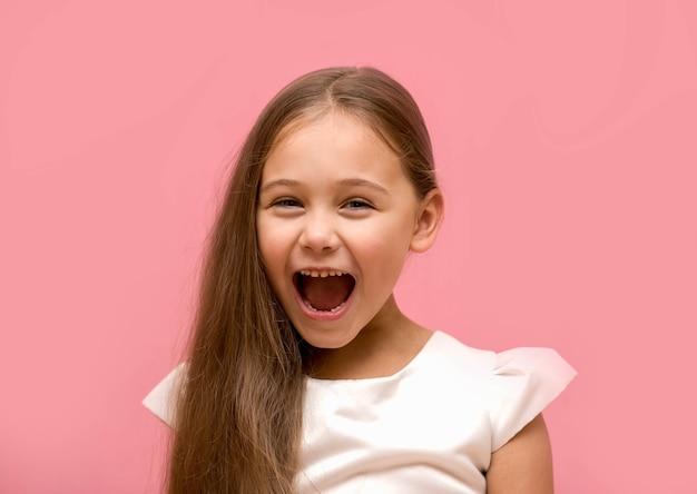 ピンクの背景に白いドレスを着て笑っている少女の肖像画