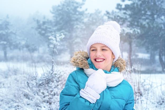 Портрет смеющейся маленькой девочки в зимней одежде.