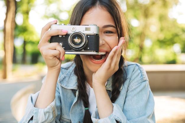 カメラを保持している自然公園の屋外のベンチに座って眼鏡をかけて笑う楽観的な幸せなかわいい若い学生の女の子の肖像画