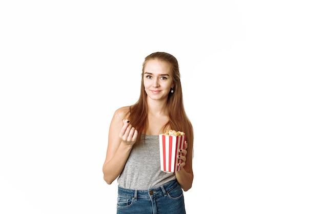 Портрет смеющейся женщины в повседневной одежде, держащей коробку для попкорна. красивая женщина улыбается.