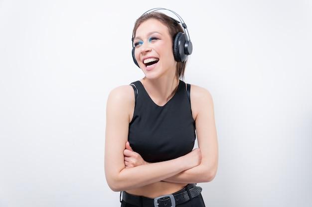 Портрет смеющейся женщины в наушниках. концепция музыкальных аксессуаров. смешанная техника