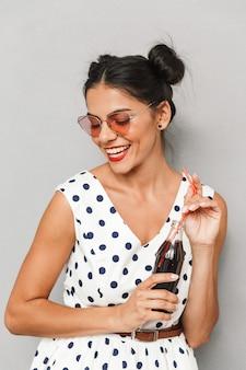 Портрет смеющейся молодой женщины в летнем платье и солнечных очках изолированы, держа бутылку с газированным напитком