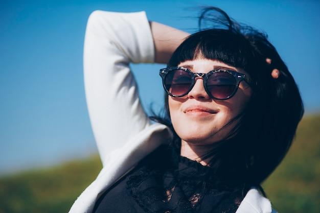 白いジャケットの公園の芝生の上のサングラスのライフスタイルブルネットの女の子の肖像画。