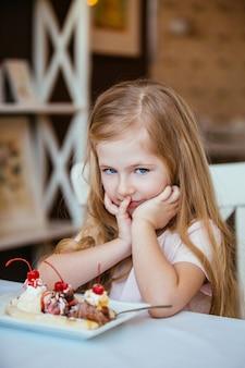 Портрет маленькой красивой девочки, сидящей в кафе за столом с блюдом из мороженого с фруктами.