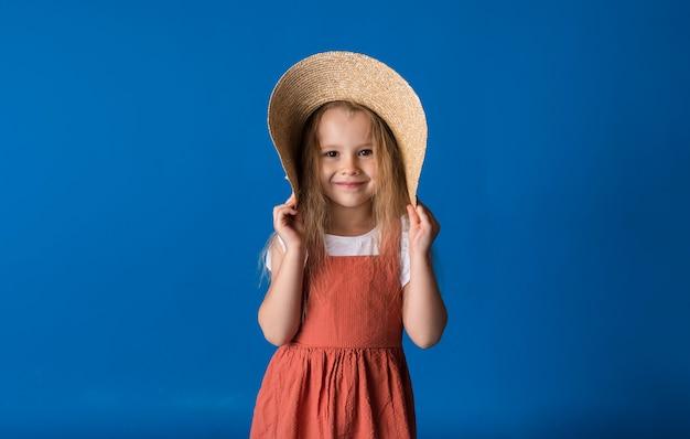 밀짚 모자에 작은 금발 소녀의 초상화는 텍스트를위한 공간이있는 파란색 표면에 선다.