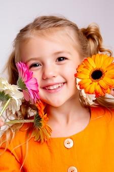 光の壁に春の花の花束と金髪少女の肖像画