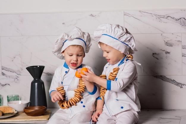 부엌에서 냄비를 들고 어린 소년 쿡의 초상화. 다른 직업. 흰색 배경 위에 격리. 쌍둥이 형제