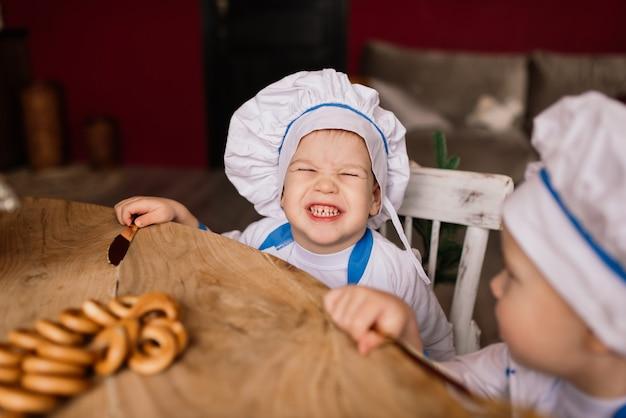 台所で鍋を持っている小さな男の子の料理人の肖像画。さまざまな職業。白い背景の上に隔離。双子の兄弟