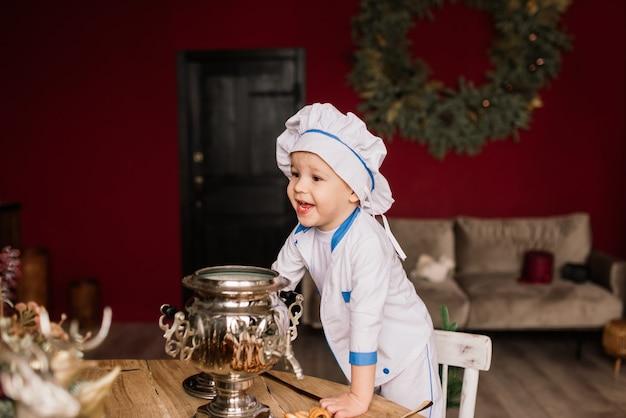 キッチンで鍋を持っている小さな男の子の料理人の肖像