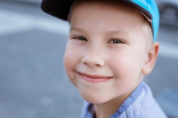 Портрет маленького мальчика в синей кепке на улице крупным планом ребенка со светлыми волосами и голубыми глазами ...