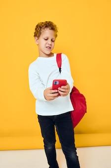 흰색 운동복을 입은 어린 소년의 휴대전화 빨간색 배낭 스튜디오 학습 개념