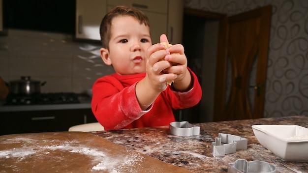 Портрет маленького мальчика, замешивающего тесто на кухне