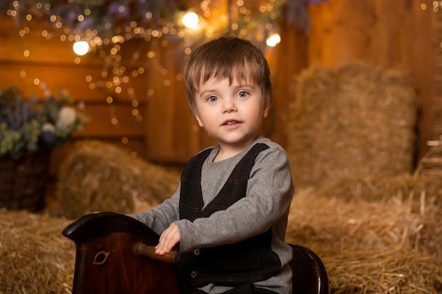 レトロな衣装を着てロッキングホースの小さな男の子の肖像画