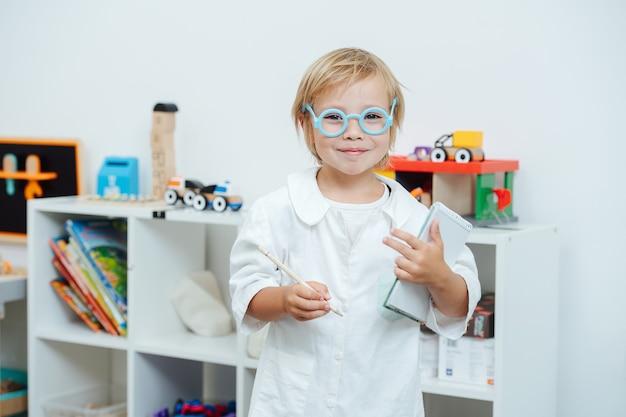 Портрет маленького мальчика, играющего врача в игрушечных очках и белом халате