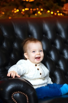 Портрет маленького мальчика, сидящего на диване и улыбающегося