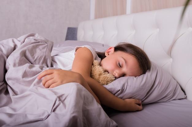 寝室のベッドでぬいぐるみと一緒に寝ているパジャマを着た小さなブルネットの少女の肖像画