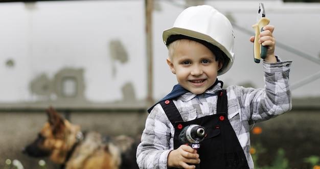 彼の手にドライバーと白いヘルメットの小さなビルダーの肖像画