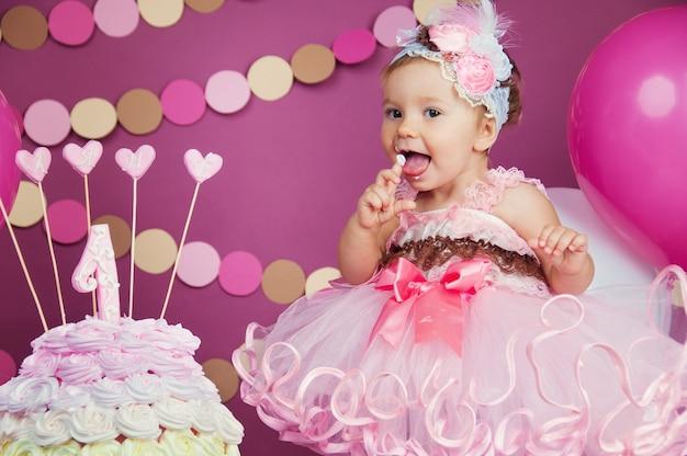 첫 번째 케이크와 함께 약간 밝은 생일 소녀의 초상화. 첫 번째 케이크를 먹고 있습니다. 스매시 케이크.