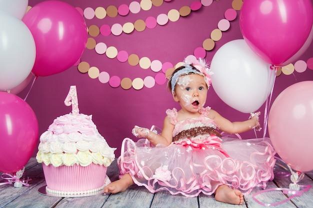 最初のケーキを持つ小さな陽気な誕生日の女の子の肖像画。最初のケーキを食べる。スマッシュケーキ。