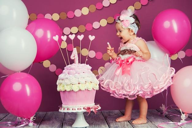 첫 번째 케이크와 함께 약간 쾌활한 생일 소녀의 초상화