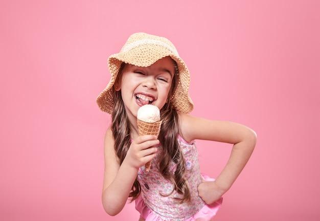 Портрет маленькой веселой девушки с мороженым на цветном фоне